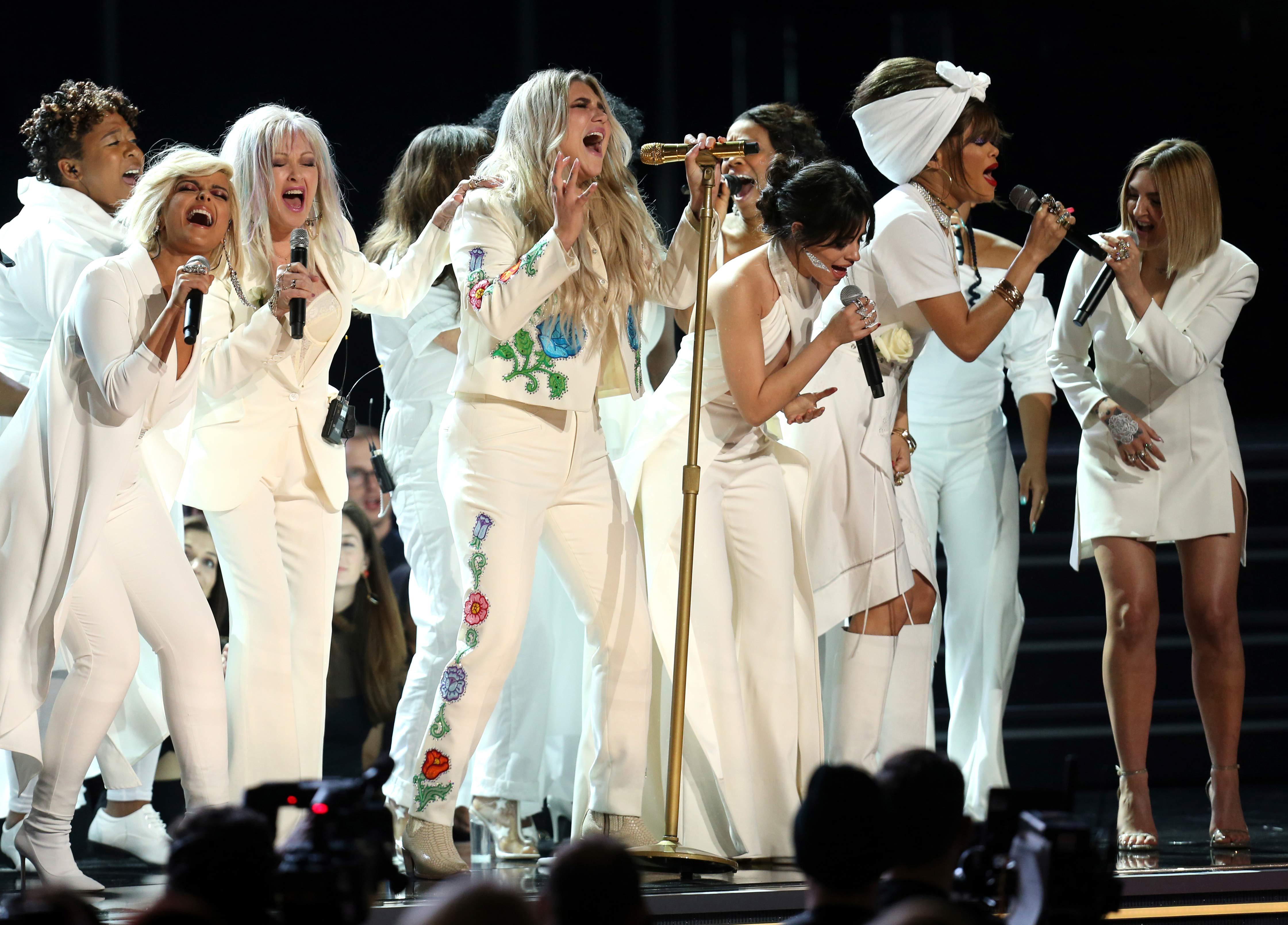"""Kesha, durante su interpretación de """"Praying"""" acompañada por (de izq a der) Bebe Rexha, Cyndi Lauper, Camila Cabello, Andra Day y Julia Michaels. (Foto: Matt Sayles/Invision/AP)"""