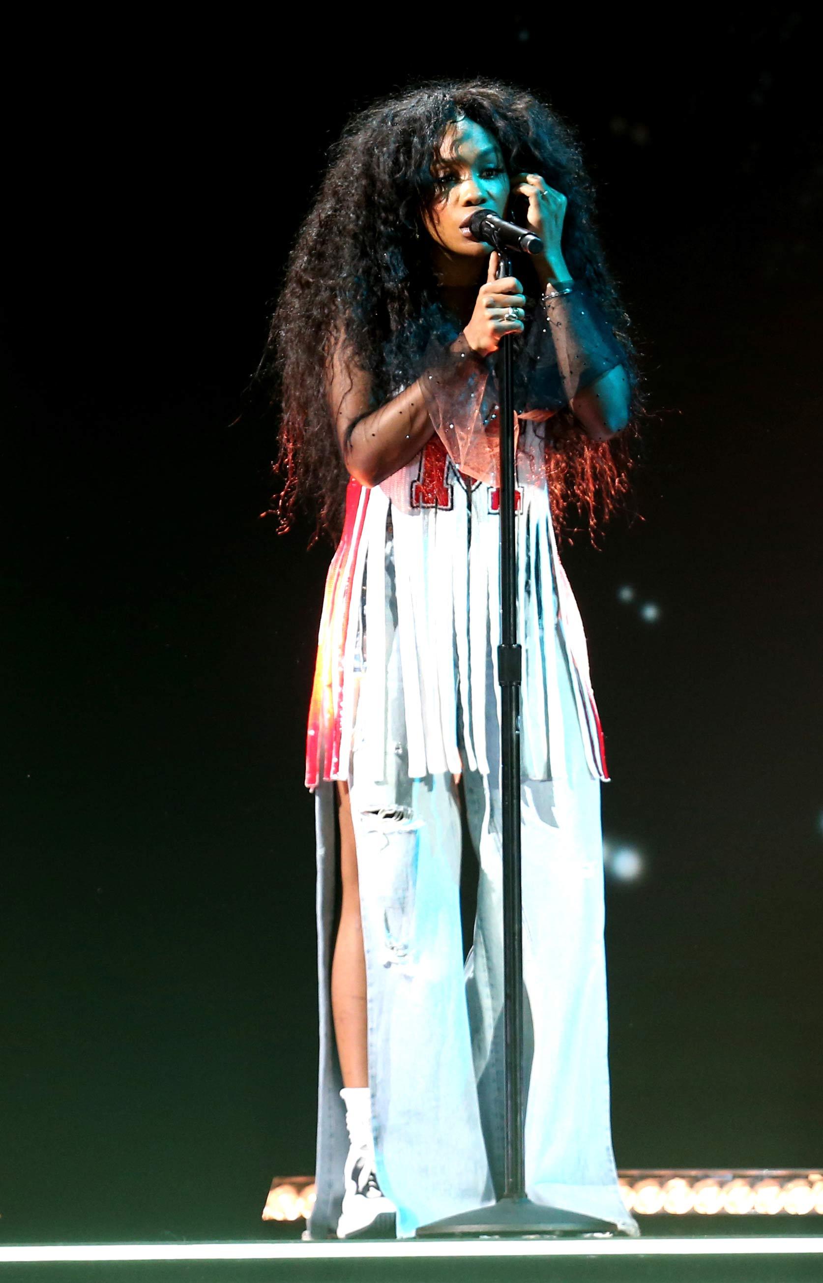SZA, que lució de blanco en la alfombra roja, mantuvo ese color a la hora de subir al escenario aunque cambió de look. (Foto: AP)