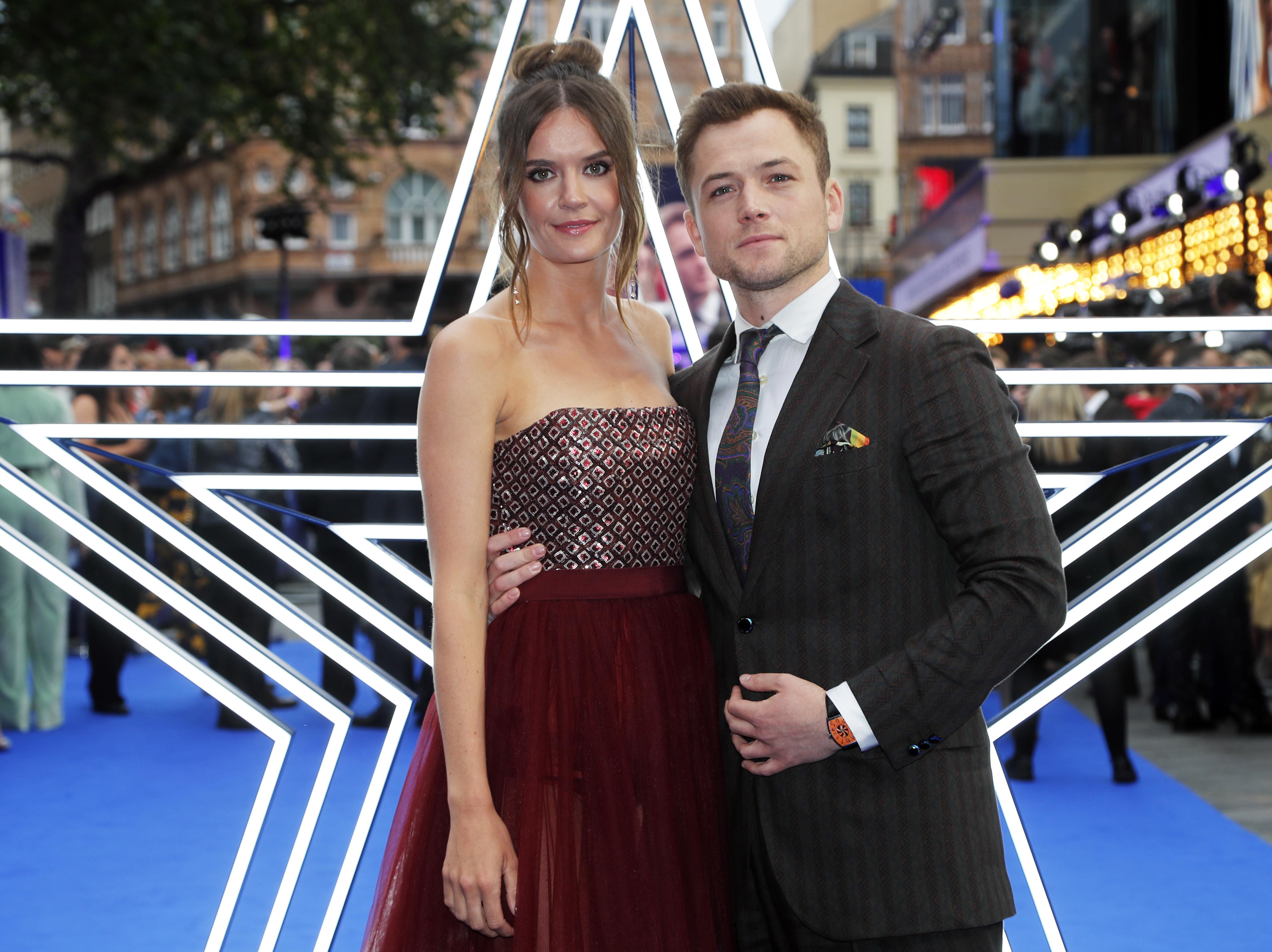 Taron Egerton, el protagonista de la cinta y su novia Emily Thomas en la alfombra azul del Odeon Luxe en Londres, (AP Photo/Frank Augstein)