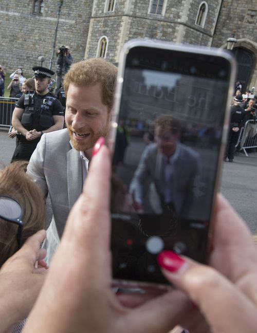 Un espectador retrata al Príncipe con su teléfono. (AP Photo/Peter Dejong)