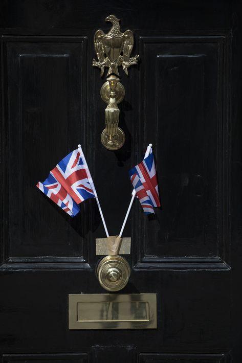 """Dos mini banderines del """"Union Jack"""" adornan la puerta de una casa en el pueblo de Windsor, donde tendrá lugar la boda real mañana sábado al mediodía.(AP Photo/Peter Dejong)"""