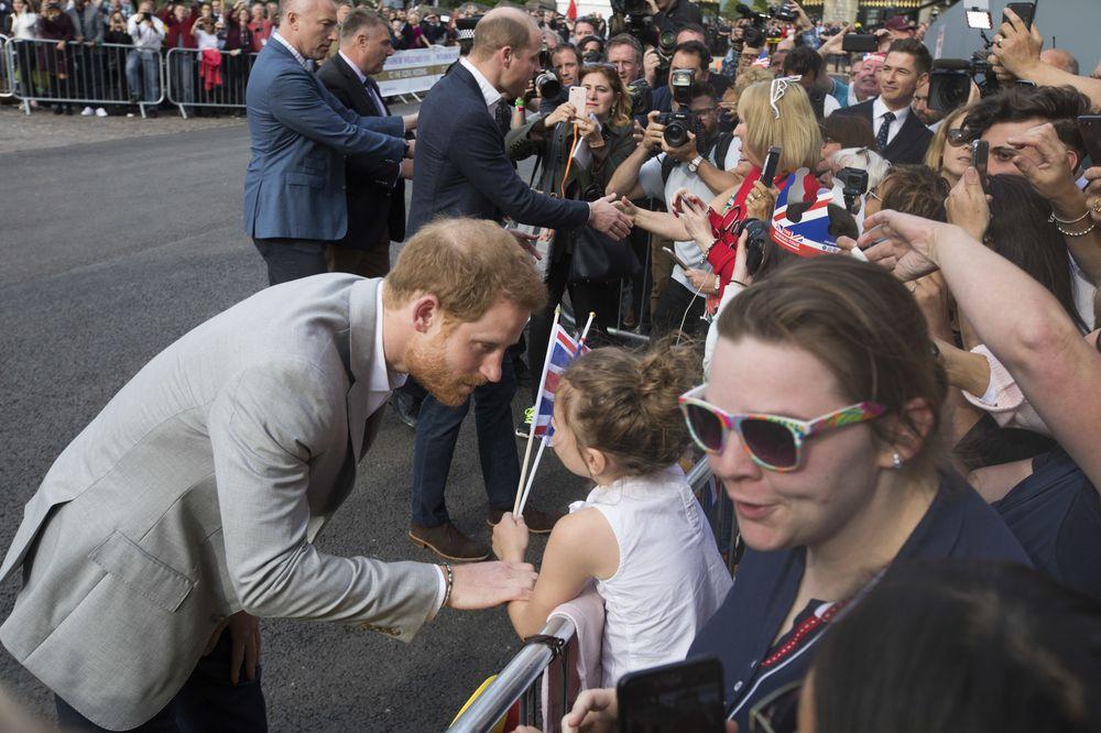 Haciendo gala de su buen humor y encanto, el príncipe Harry conversa con una niñita el día antes de la boda real. (AP Photo/Peter Dejong)