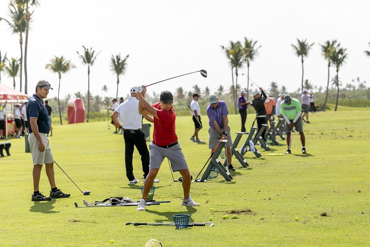 Jugadores calientan en el mini campo de golf. (Suministrada)