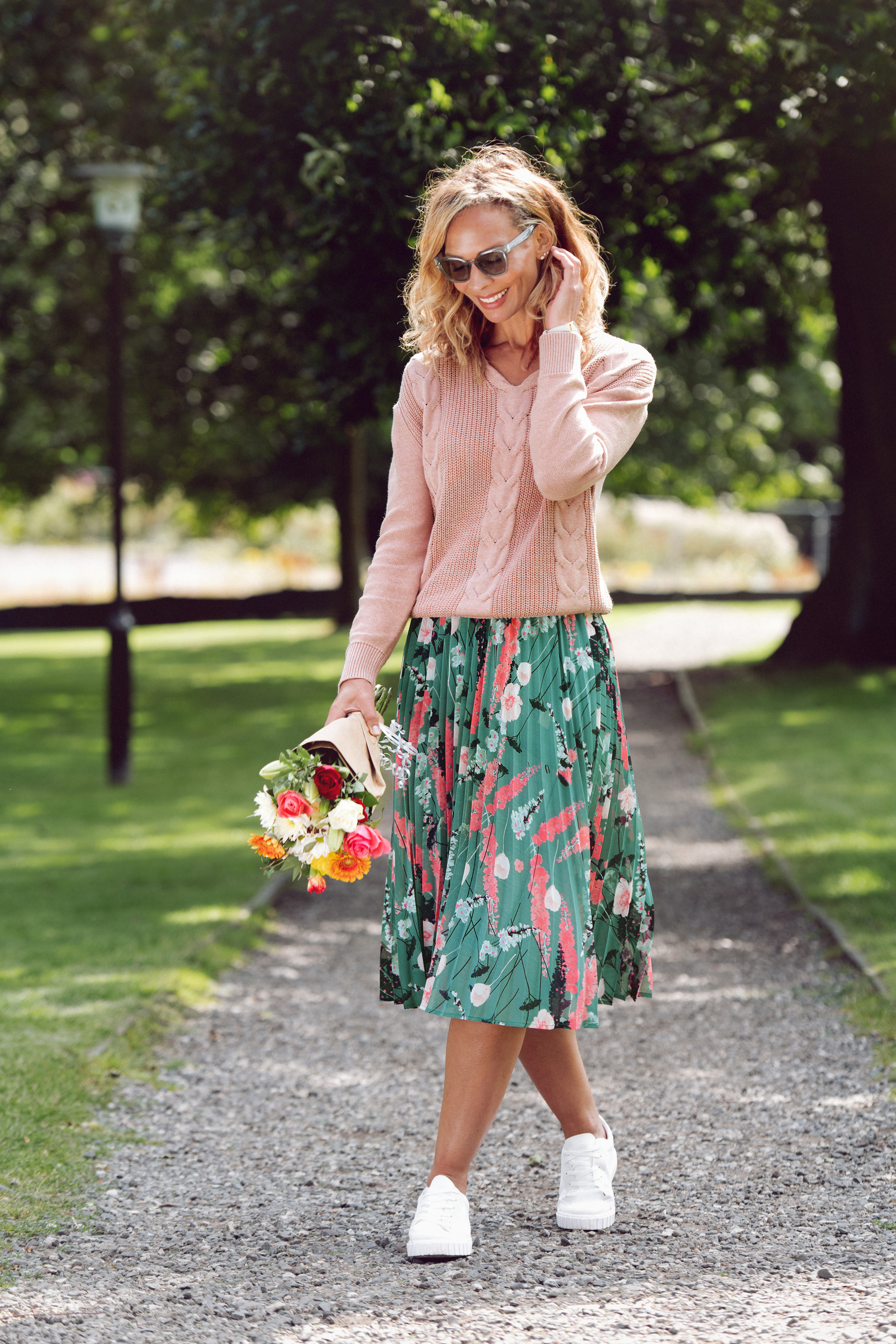 Una de las combinaciones más buscadas entre mujeres que quieren estar cómodas sin dejar de verse a la moda es la de la falda midi plisada con tenis. (WGSN)