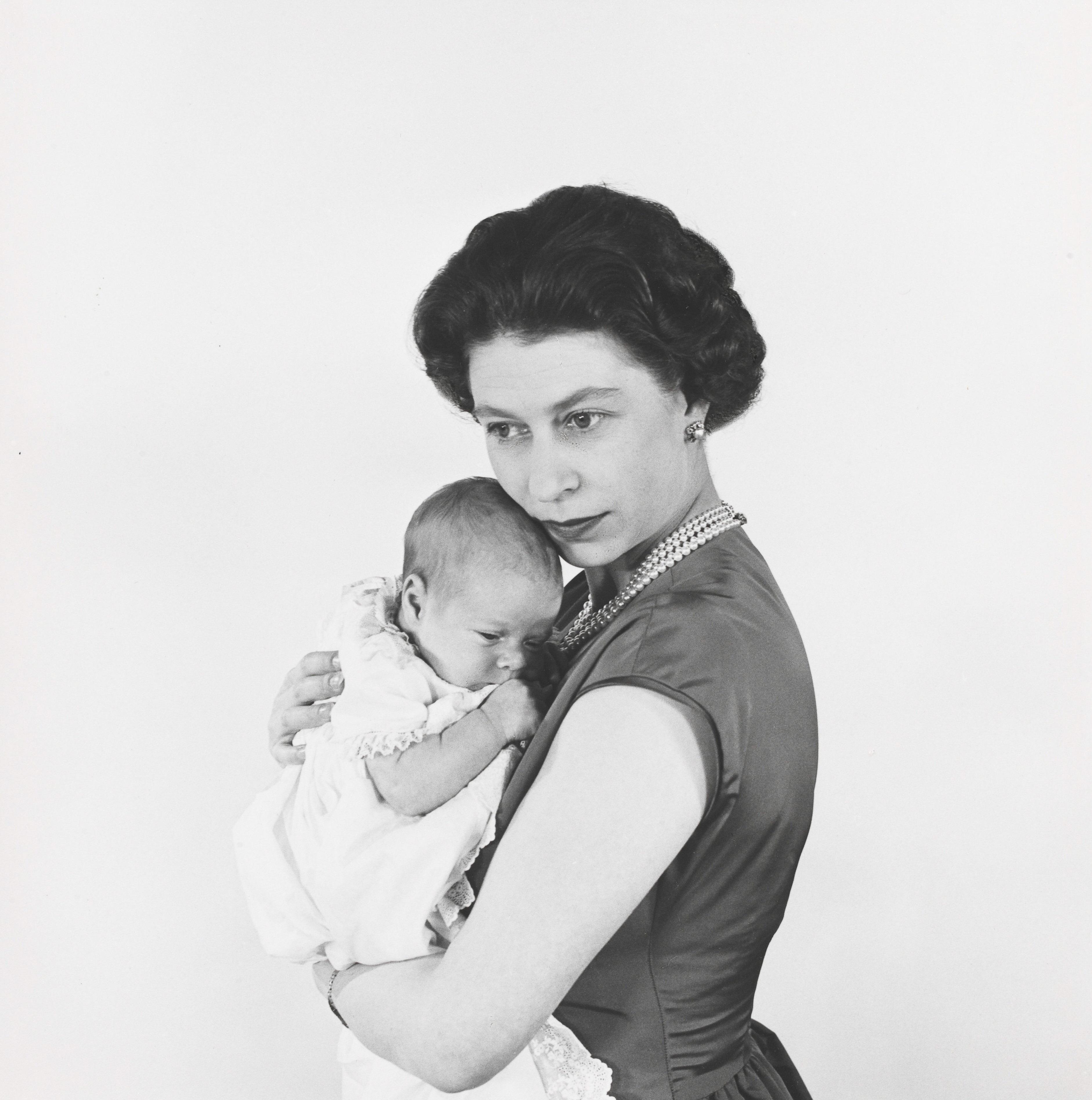 """La reina Elizabeth II de Inglaterra sostiene al príncipe Andrew. La imagen data del 1960 y formó parte de la exposición """"Queen Elizabeth II by Cecil Beaton: A Diamond Jubilee Celebration"""" que se llevó a cabo en el 2012 en el Museo Victoria & Albert. (Archivo)"""