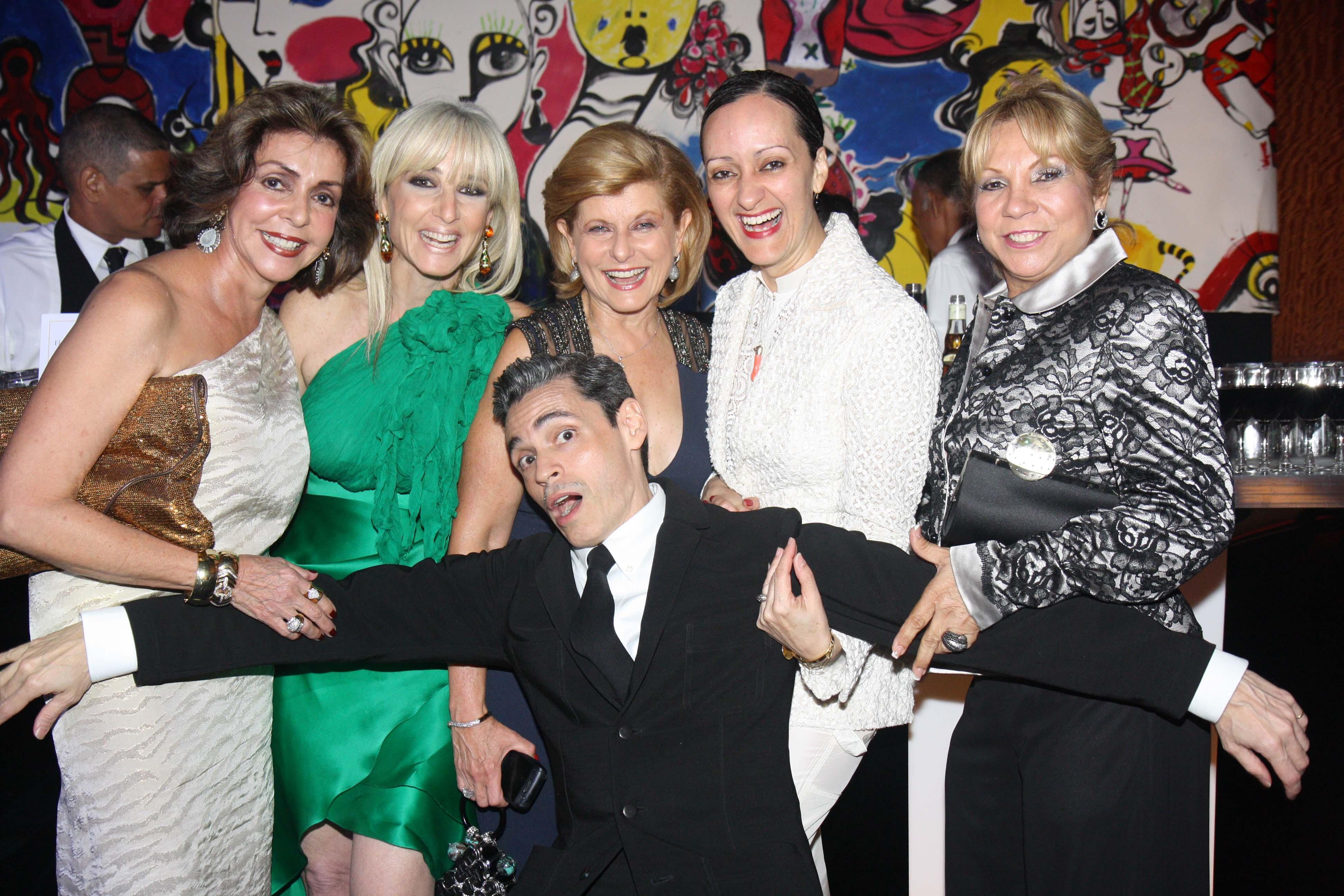 Haciendo gala de su sentido del humor, Ruben Toledo se lanza -ante el lente de Magacín- sobre Marisita Cortés, Mercy Short, Zoila Levis, Isabel Toledo y Aidita Gnocchi, en la inauguración de la exhibición de su esposa. (Foto Archivo GFR Media)