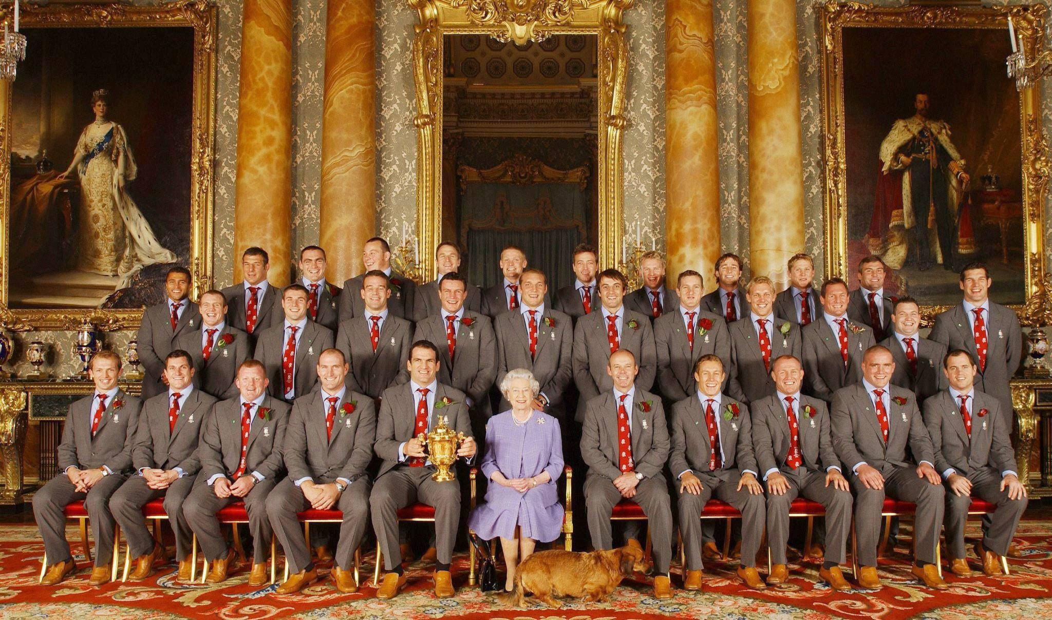 La reina de Inglaterra posa con los jugadores del equipo nacional de rugby, durante una recepción oficial en el Palacio de Buckingham para celebrar la consecución del Campeonato del Mundo de Rugby en agosto de 2003. (Archivo)