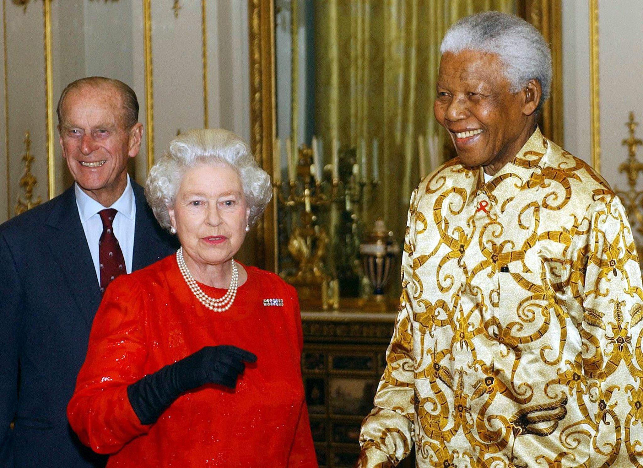 La reina y el duque de Edimburgo saludan al expresidente de África del Sur, Nelson Mandela durante una recepción en el Palacio de Buckingham en octubre de 2003. En esa ocasión se celebró el centenario de la fundación Rhodes Trust, iniciada por el empresario Cecil John Rhodes en el siglo 19, para proveer becas a estudiantes del mundo para estudiar en la Universidad de Oxford. (Archivo)