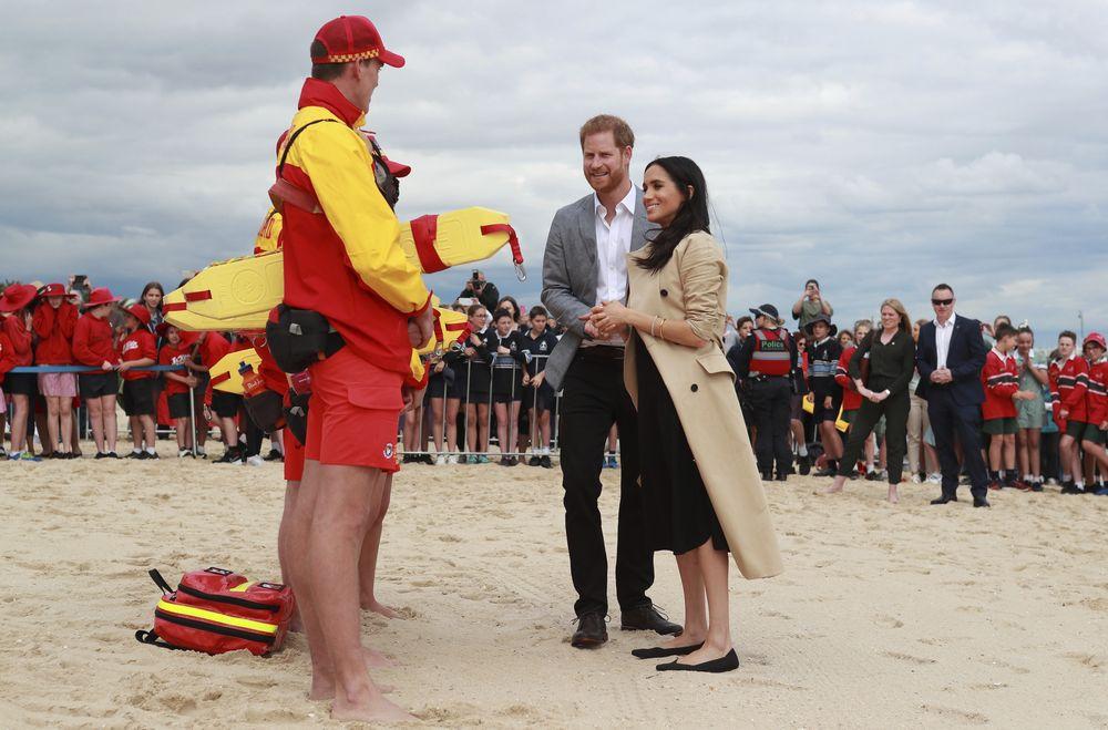Los duques de Sussex saludaron a los salvavidas de las playas del sur de Melbourne, en Australia. Meghan se decantó por un estilo más cómodo que incluyó vestido negro, abrigo kaki y zapatos sin tacón. (AP)