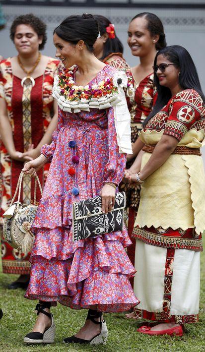 """Meghan no dudó en compartir las costumbres de los países que visitó. En esta foto luce una estola de flores sobre un """"maxidress"""" rojo estampado. (AP)"""