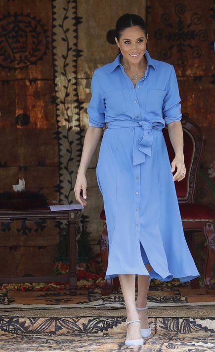 """En un """"look"""" más casual y cómodo, Meghan optó por un vestido camisero azul claro en su visita a Tupou College, en Tonga. (AP)"""