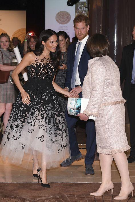 """Los duques de Sussex a su llegada a la premiación de la Sociedad Geográfica Australiana. Meghan luce un vestido en tono """"nude"""" con siluetas de aves negras, de Oscar de la Renta. (AP)"""