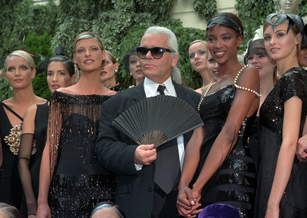 Luego de un desfile de Chanel en París en julio de 1996. El modisto posa junto a las modelos Linda Evangelista y Naomi Campbell, entre otras. (AP)