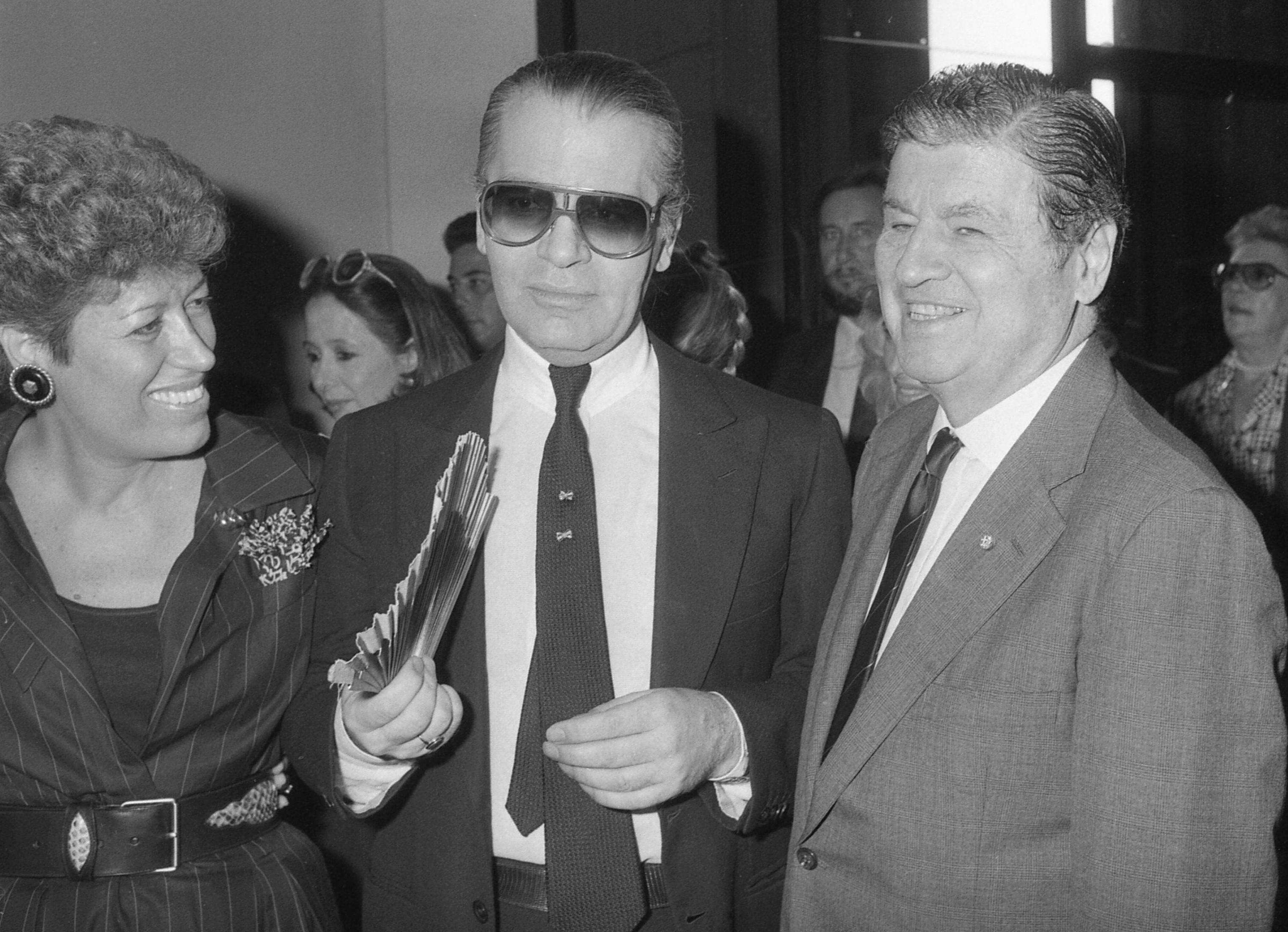 Carla Fendi, portavoz de la familia Fendi, Karl Lagerfeld y el embajador estadounidense, Maxwell Rabb, durante la apertura de una exhibición en la Galería Nacional de Arte Moderno en Roma en octubre de 1985. (AP)