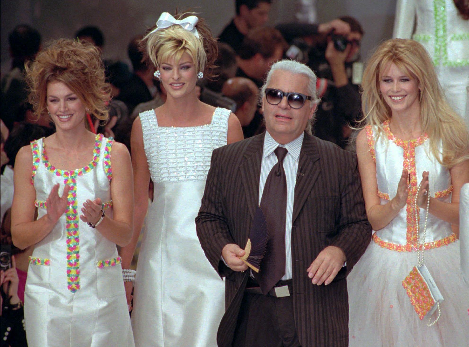 """Lagerfeld siempre estuvo rodeado de las modelos más famosas. En este desfile celebrado en París en octubre de 1995 sale a saludar al público acompañado de las """"super models"""" Cindy Crawford, Linda Evangelista y Claudia Schiffer. (AP)"""