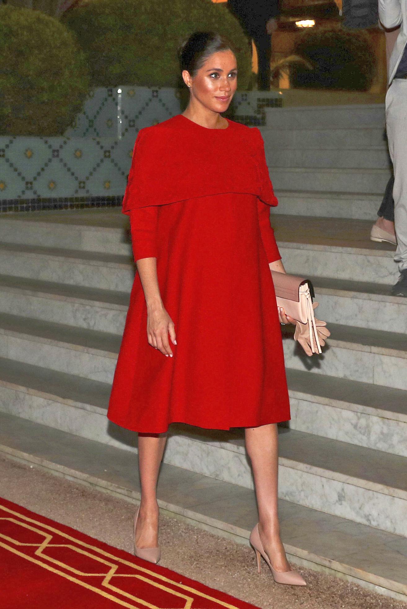 Meghan llegó a Marruecos luciendo un amplio vestido rojo con mangas tres cuartos de una pequeña capa sobre los hombros. La pieza es una creación de la casa de moda Valentino. (AP)
