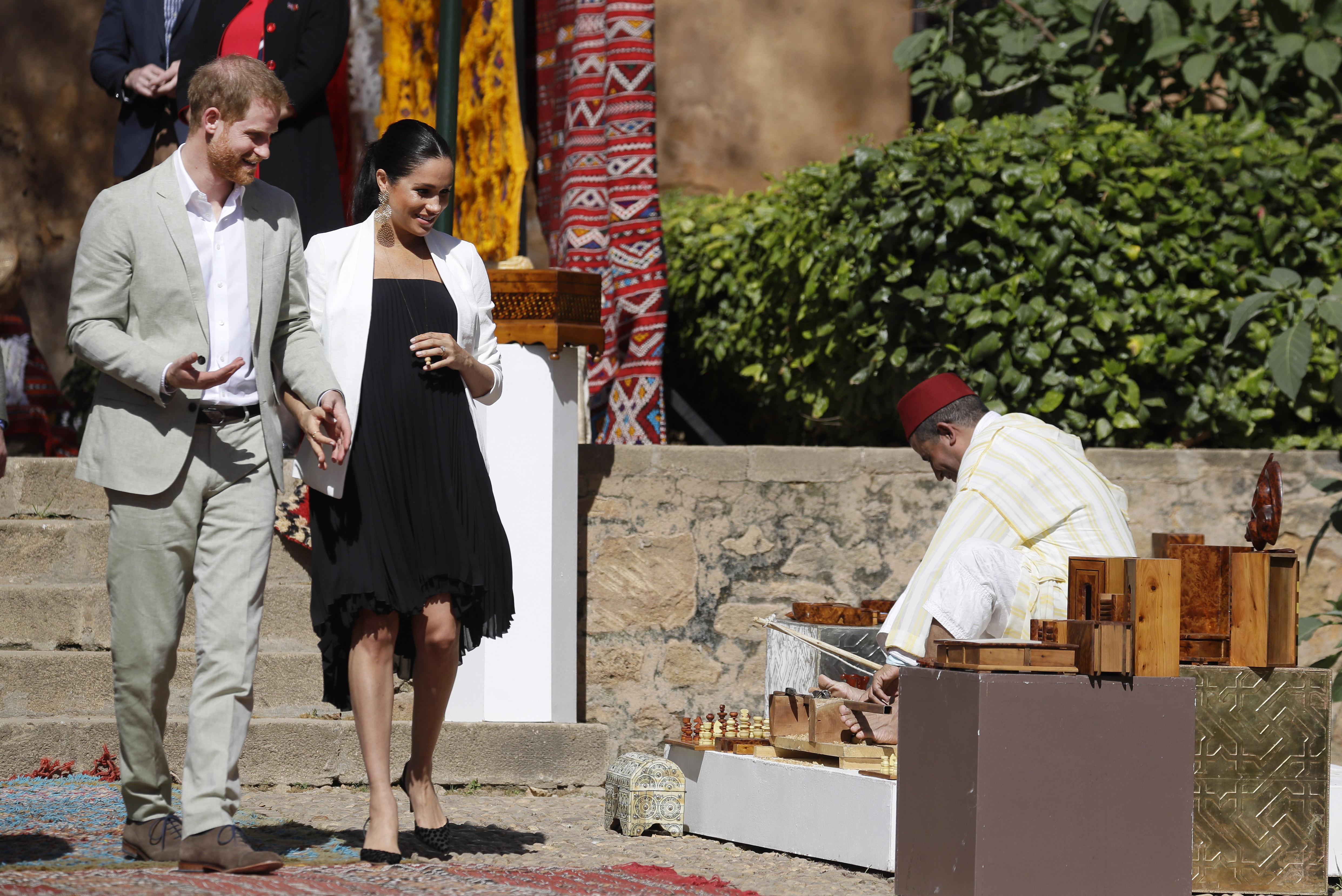 Los duques de Sussex visitaron la famosa Alcazaba de los Udayas, uno de los lugares emblemáticos de la capital marroquí, donde recorrieron su jardín andalusí. Para la ocasión, Meghan seleccionó un vestido negro corto plisado con chaqueta blanca. (AP)