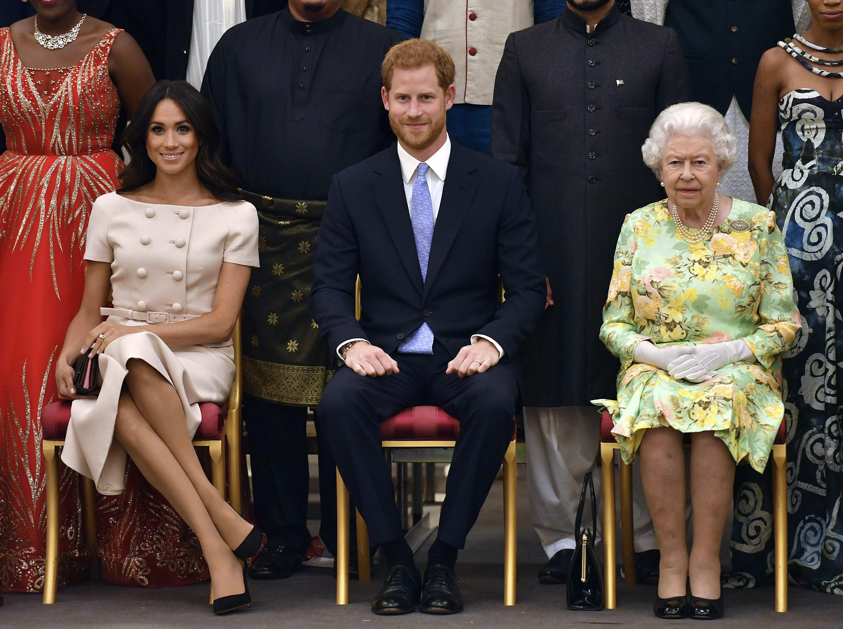 """A finales de junio de 2018 Meghan rompió uno de los protocolos durante la entrega de los Premios a los Jóvenes Líderes de la Reina. La duquesa olvidó la norma que establece que debe sentarse con las piernas una al lado de la otra o cruzadas a la altura de los tobillos -pose conocida como """"inclinación de la princesa""""-, y las cruzó por los muslos. (Archivo)"""