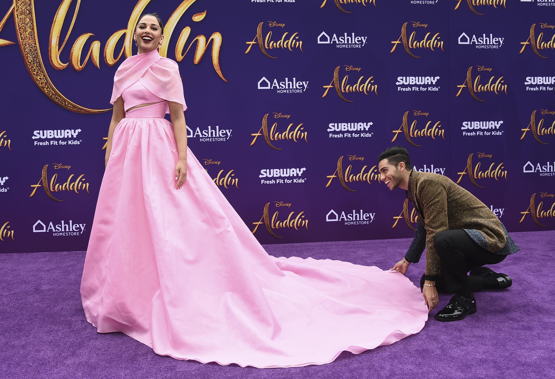 Mena Massoud acomoda la cola del vestido de su coprotagonista, Naomi Scott, que lució un modelo escote palabra de honor, bolsillos y minicapa cruzada de Brandon Maxwell. (Photo by Jordan Strauss/Invision/AP)