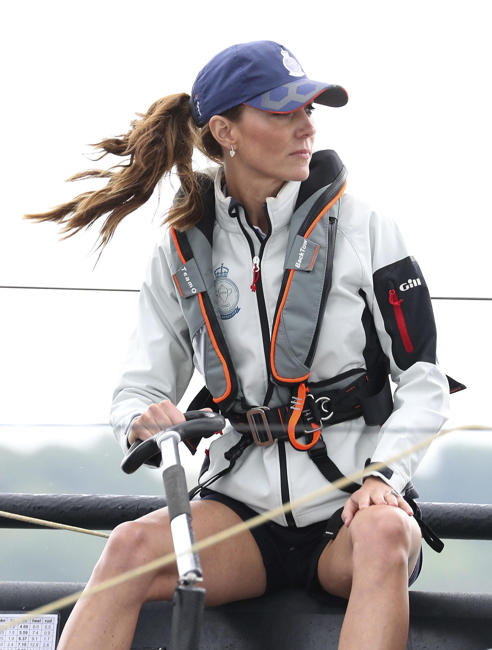 Kate Middleton lució pantalones cortos azul marino y chaqueta gris para cubrirse del viento. (AP)