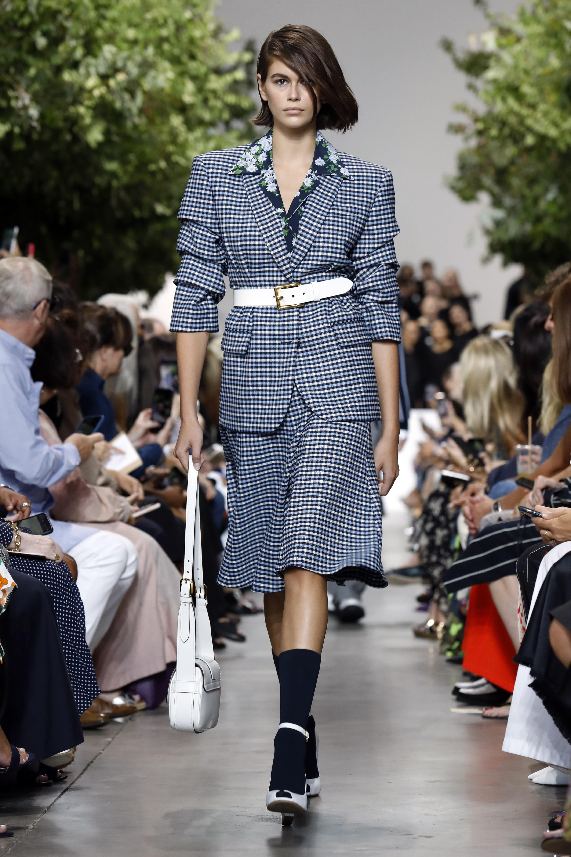 Kaia Gerber lució traje de chaqueta y falda de cuadros sobre camisa de flores. (AP)