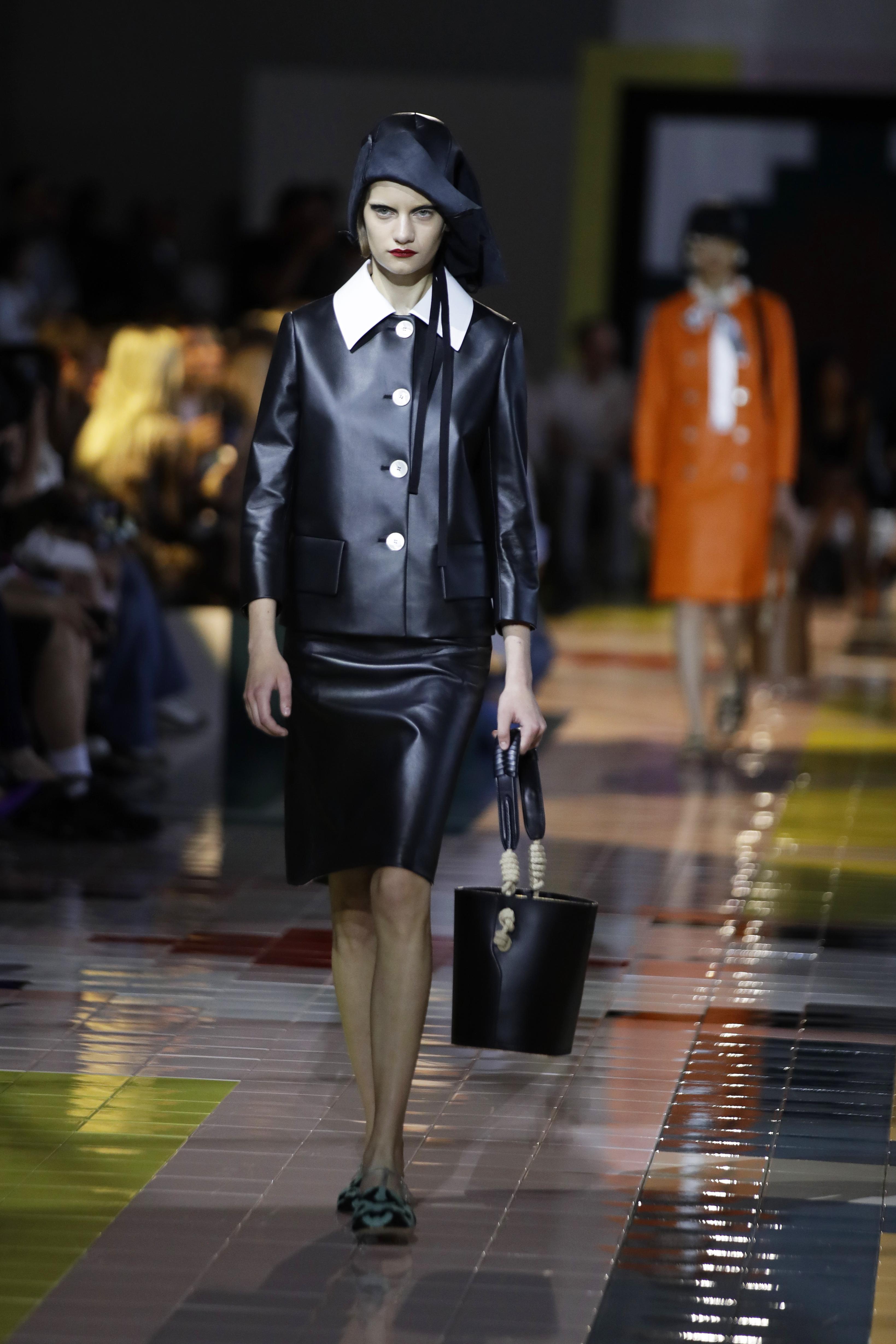 """La chaqueta negra con cuatro botones verticales en blanco compone un """"look"""" elegante con las solapas de una camisa blanca que se colocan por encima de la chaqueta y debajo una falda negra de silueta lápiz y botas altas. (AP)"""