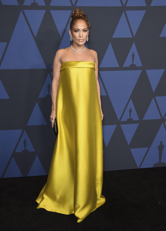 """El """"look""""de Jennifer López fue uno de los más celebrados de la noche. Se trataba de un vestido satinado en color dorado de Reem Acra, con escote palabra de honor y silueta holgada que tenía un lazo en la espalda. Además, tenía un moño trenzado con collar y pendientes de diamantes. Foto Jordan Strauss/Invision/AP"""