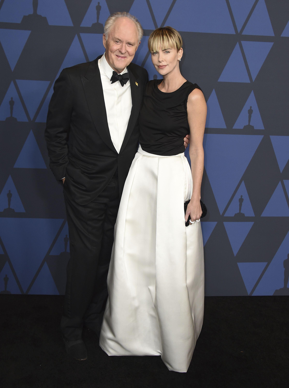 John Lithgow, y Charlize Theron La actriz, famosa por su estilo en la alfombra roja, llevó un vestido de Tom Ford y un nuevo recorte con flequilo. Foto Jordan Strauss/Invision/AP