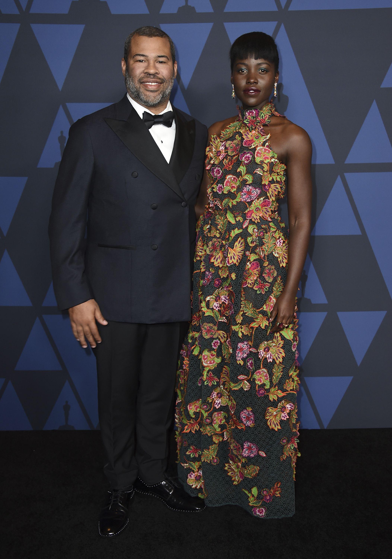 Jordan Peele y Lupita Nyong'o, con una creación de encaje floreado de Givenchy. Foto Jordan Strauss/Invision/AP