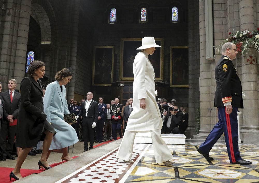 La princesa Charlene lució un elegante conjunto de abrigo, pantalón y sombrero blanco, mientras que la princesa Estefanía optó por un ajuar sobrio, con chaqueta negra y guantes de cuero y la princesa Carolina llamó la atención por su abrigo azul claro. (AP)