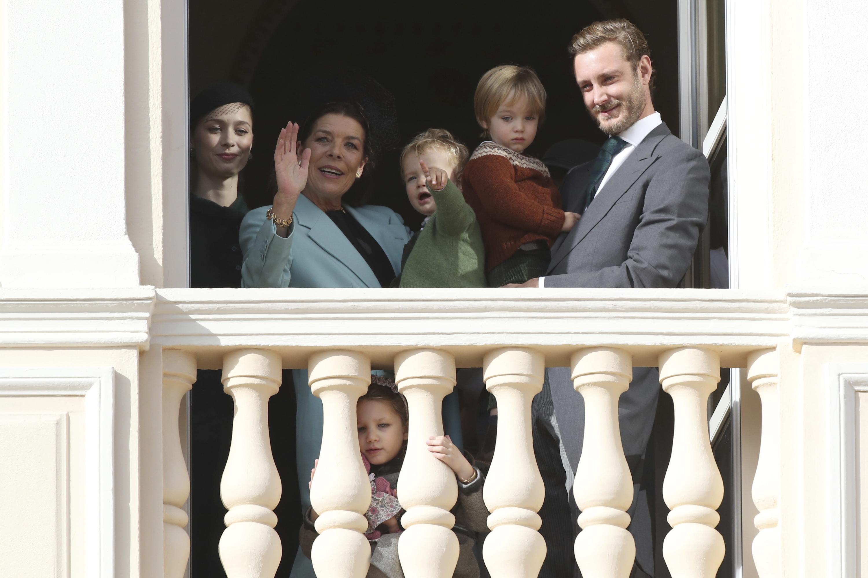 La princesa Carolina saluda desde uno de los balcones del palacio, en compañía de Stefano Casiraghi, Beatrice Borromeo y sus nietos Francesco, India y Stefano. (AP)