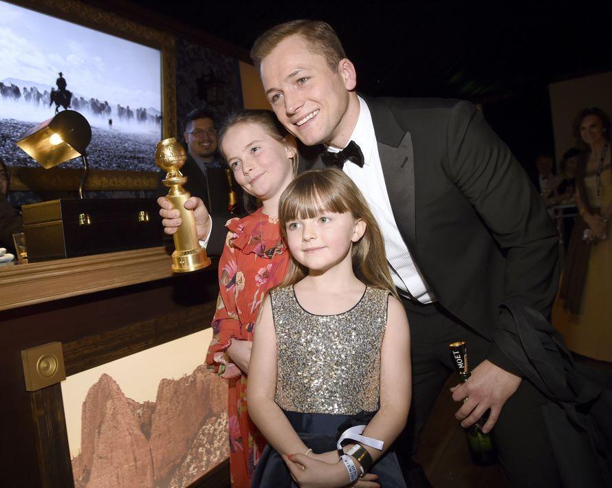 """Taron Egerton, que ganó un Golden Globe por su interpretación en la biografía de Elton John """"Rocketman""""y sus hermanitas Marie y Rosie (AP Photo/Chris Pizzello)"""