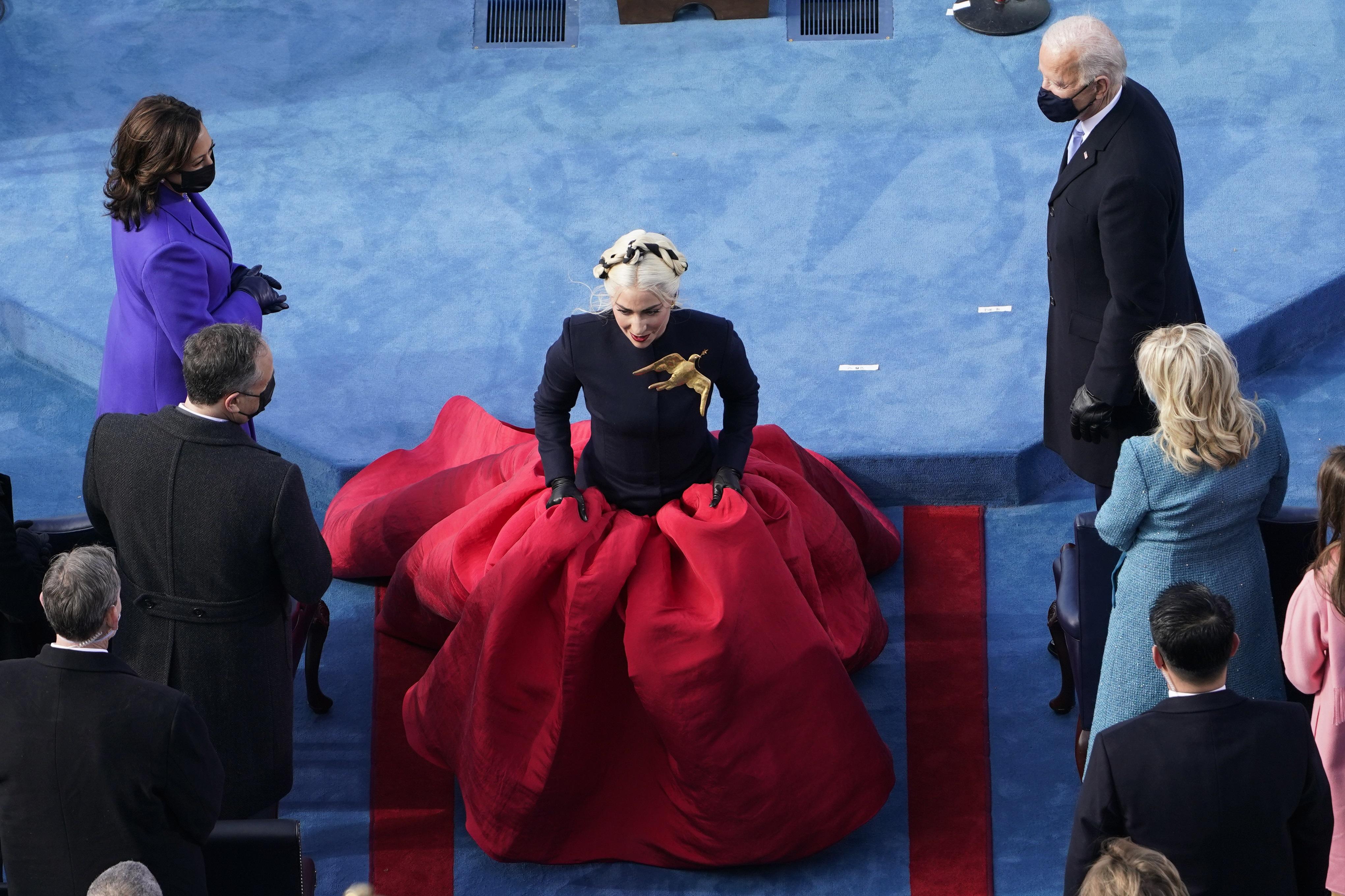 Lady Gaga cantó el himno nacional de Estados Unidos ataviada con un vestido compuesto por un top negro de cuello alto y mangas largas y una vaporosa falda roja de la casa Schiaparelli Couture. El toque más llamativo fue un broche dorado en forma de paloma que llevó sobre el lado izquierdo del pecho. (AP)