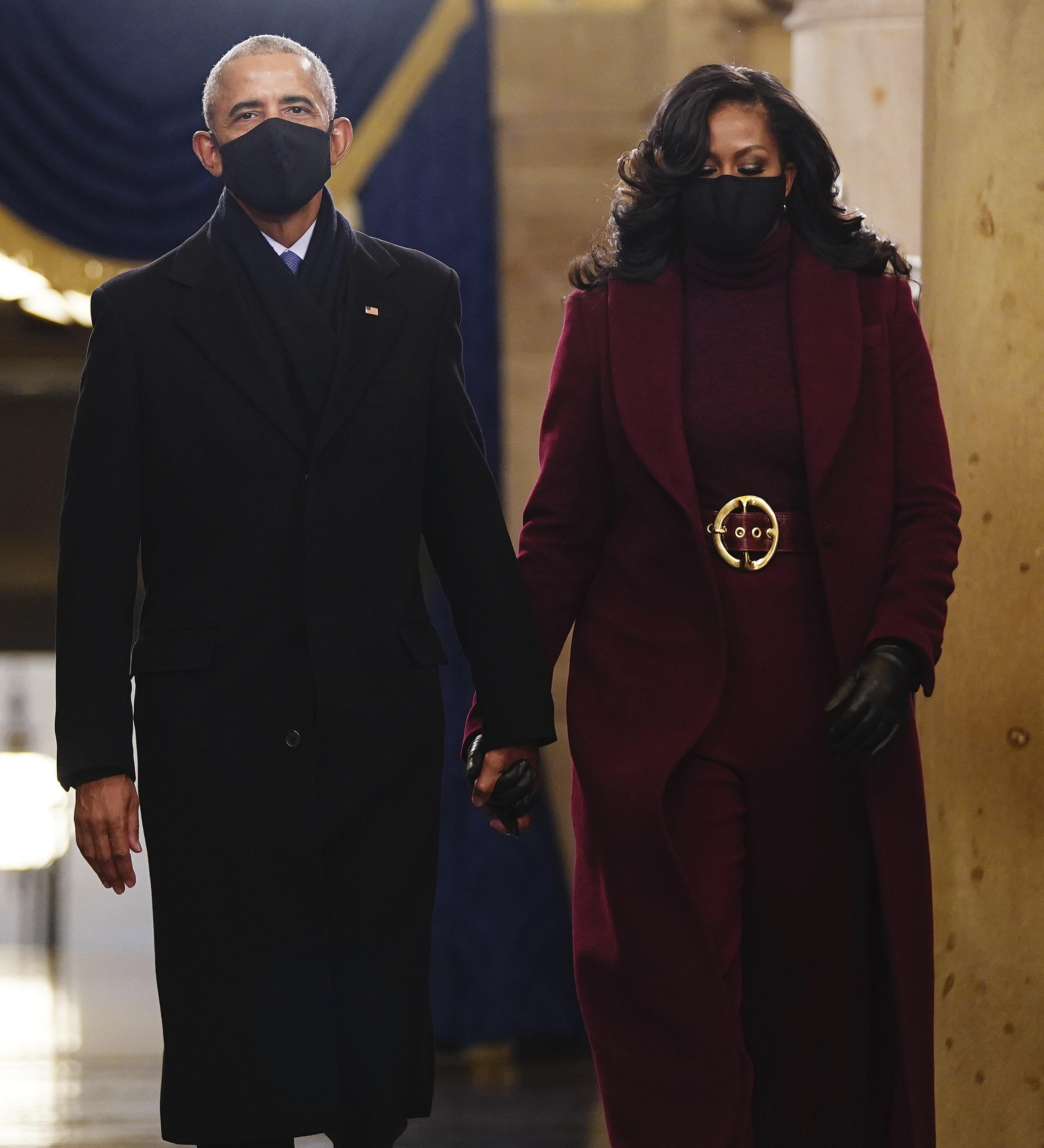 Michelle Obama -quien llegó de la mano con su esposo, el expresidente Barack Obama- lució un conjunto en tono borgoña compuesto por un pantalón de pierna ancha, un jersey de cuello alto y abrigo capa del diseñador Sergio Hudson. (AP)