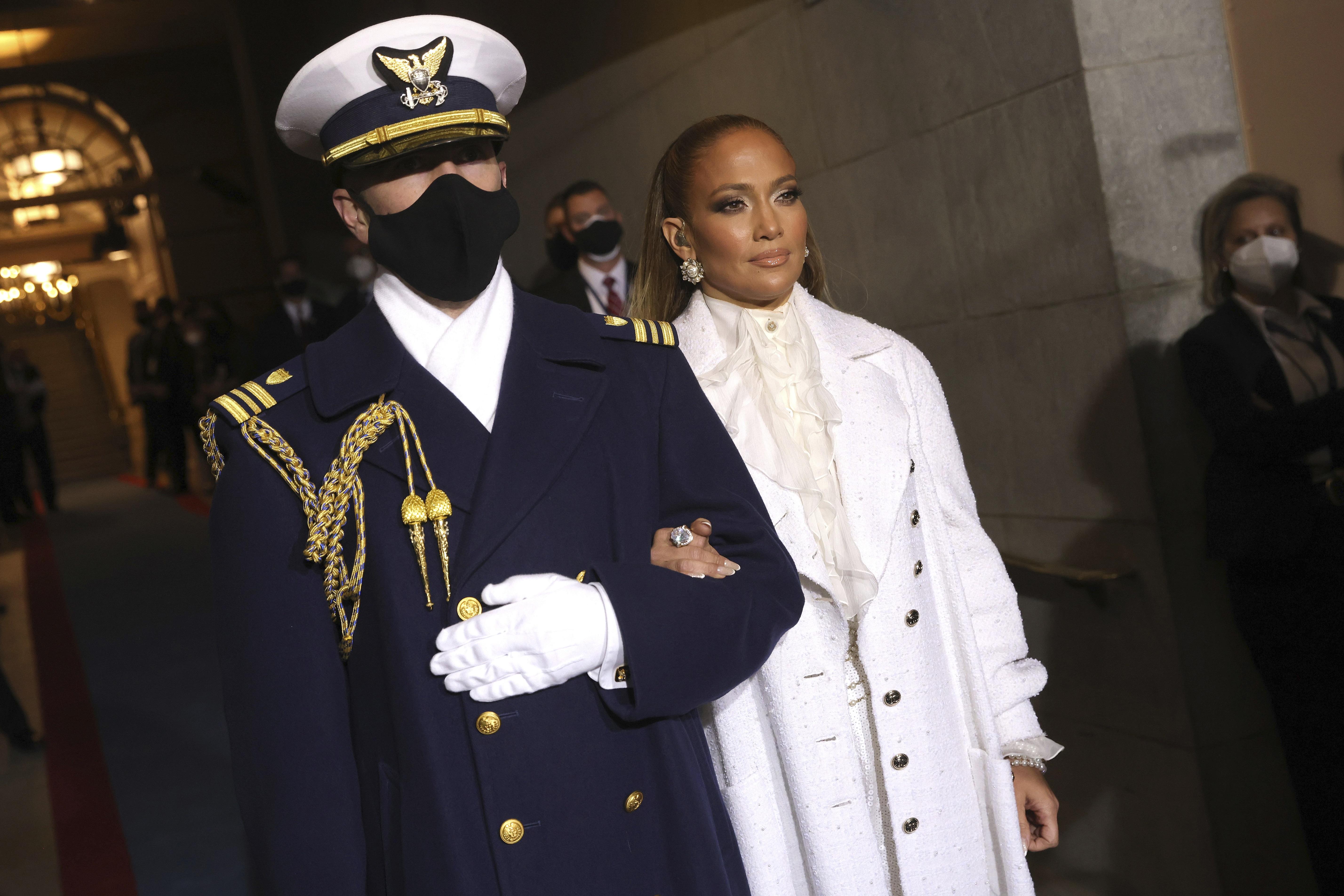 """Jennifer López entonó los temas """"America the Beautiful"""" y """"Let's Get Loud"""" en la ceremonia. Para la ocasión optó por un glamouroso conjunto de pantalón, abrigo y blusa de cuello amarrado en color blanco de la casa de moda francesa Chanel. (AP)"""