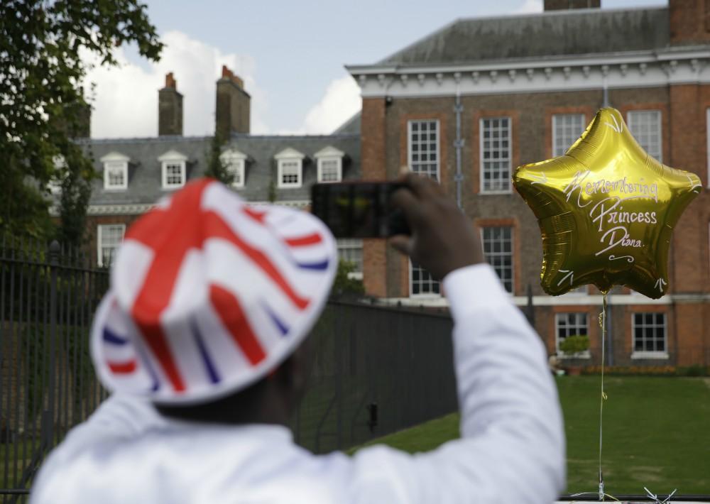 El admirador de la realeza, Joseph Afrane, toma una foto de un globo colocado junto a las puertas del Palacio de Kensington en Londres. (Foto: AP)