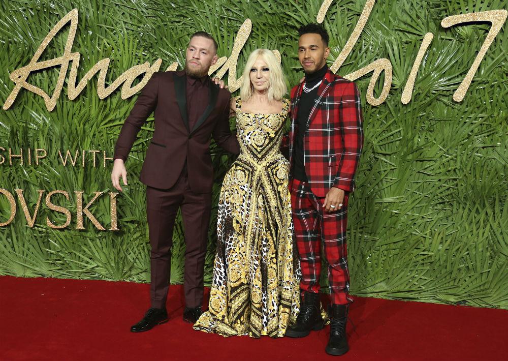 Donatella Versace, galardonada como icono de moda, posó acompañada del luchador Conor McGregor y del corredor de Fórmula Uno, Lewis Hamilton. (Foto: AP)