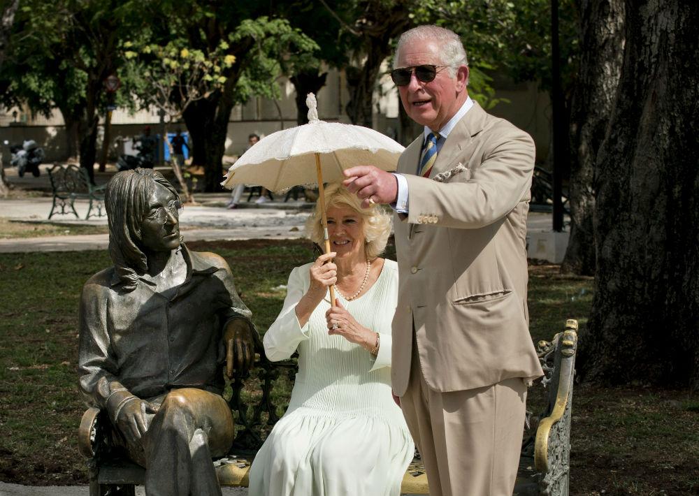 El heredero de la corona británica y su esposa complacieron a la prensa y con una sonrisa se sentaron en el banco donde descansa la efigie en bronce de John Lennon. (AP)