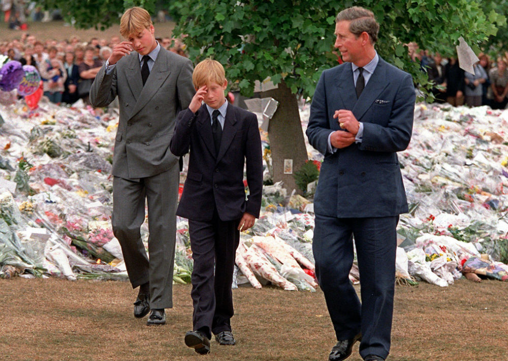 5 de septiembre de 1997. El príncipe de Gales acompaña a sus hijos, los príncipes William y Harry, mientras caminan el Kensington Palace y observan los tributos a la princesa Diana tras su trágica muerte. (AP)