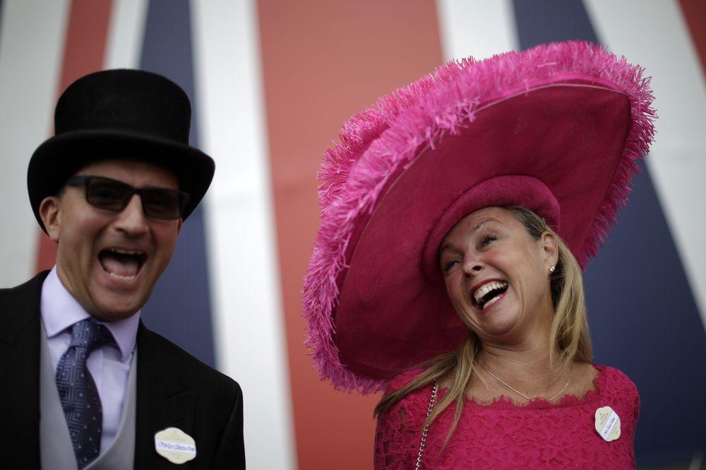 La espectadora lleva puesto un sombrero de gran tamaño con una tela de fibras largas, color rosado brillante. (Foto: AP)