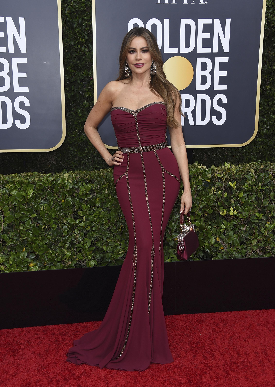 """Sofía Vergara, como de costumbre, lució un vestido """"strapless""""y ceñido al cuerpo color vino, Dolce & Gabbana. (AP)"""