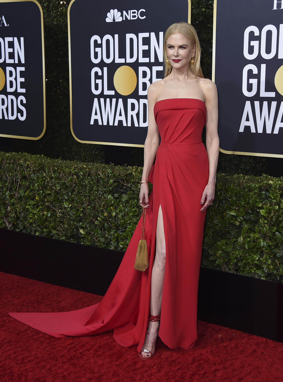 """Nicole Kidman optó por un clásico vestido """"strapless""""tipo columna en rojo, de Versace y pendientes de oro, tipo chandelier. (AP)"""