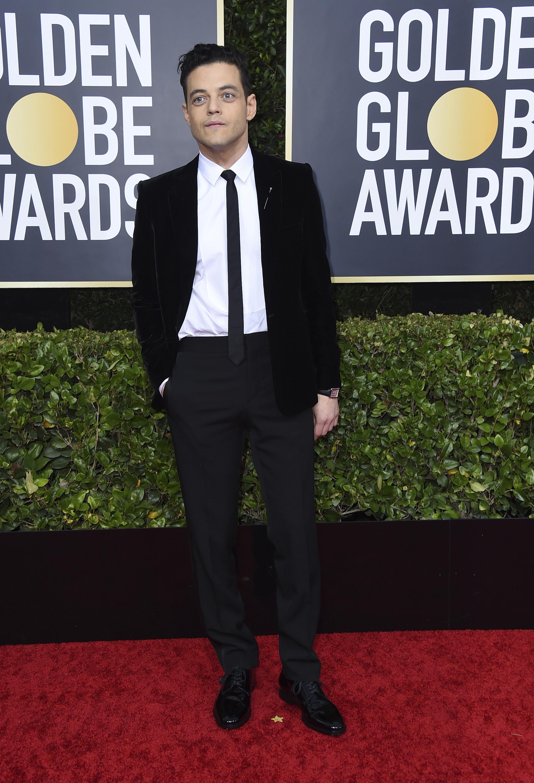 """Rami Malek, de negro, con un entalle ültra skinny""""y corbata estrecha, de Saint Laurent by Anthony Vaccarello y joyas Cartier. (AP)"""