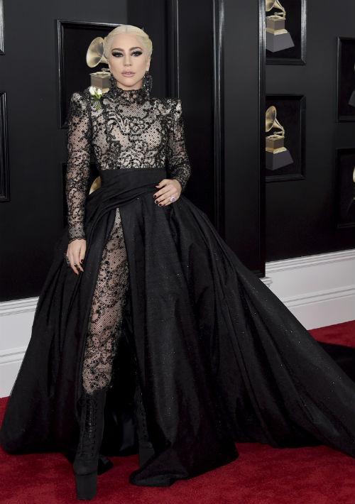 """No solo impactó con su presentación n tarima, también a su llegada Lady Gaga encendió las redes sociales con este """"jumpsuit"""" en encaje negro y amplia sobrefalda, creación de Armani Privé. (Foto: AP)"""