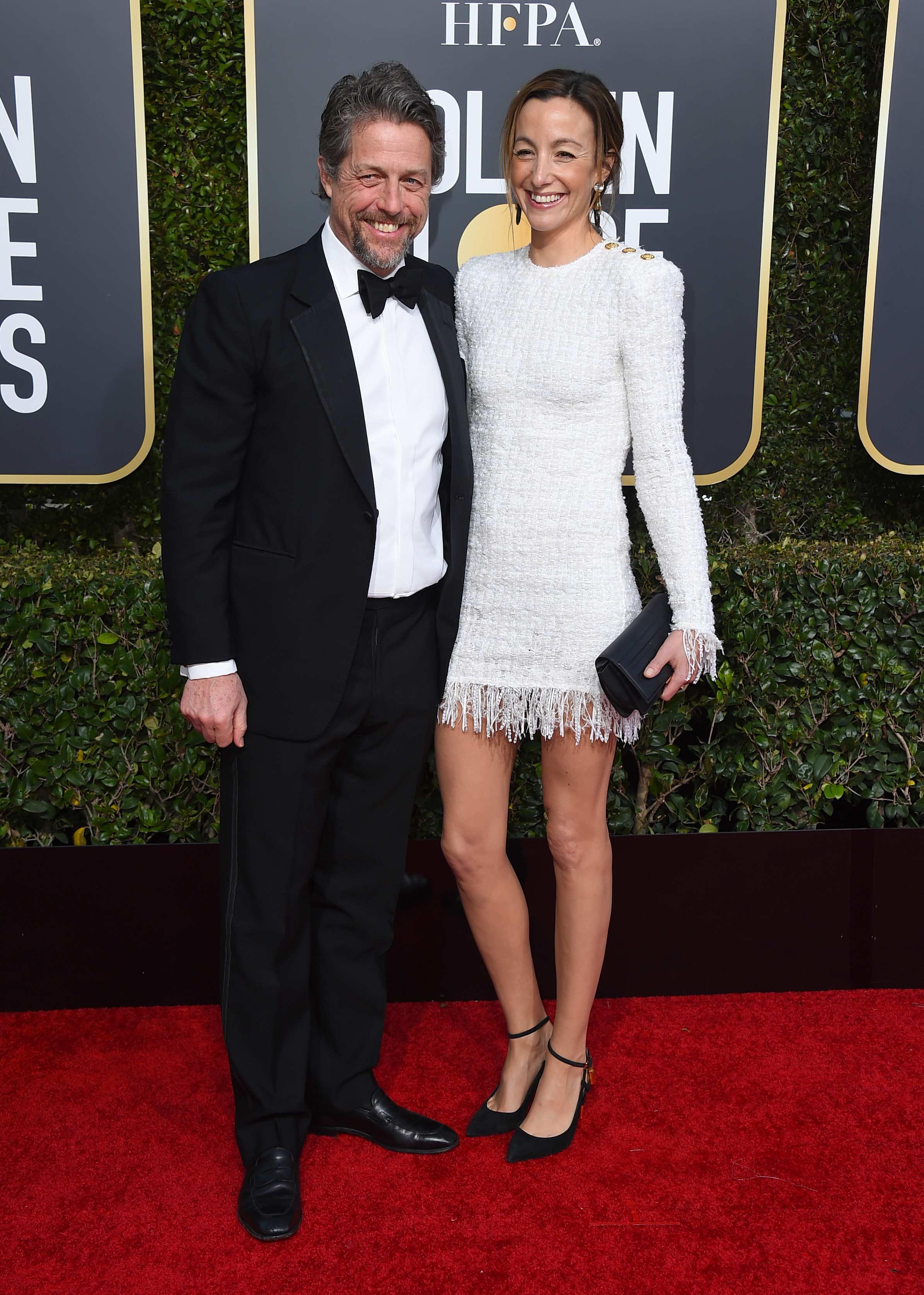 El actor británico Hugh Grant junto a su esposa, la actriz sueca Anna Eberstein, quien se robó las miradas con su mini-dress con flecos. (Foto: AP)