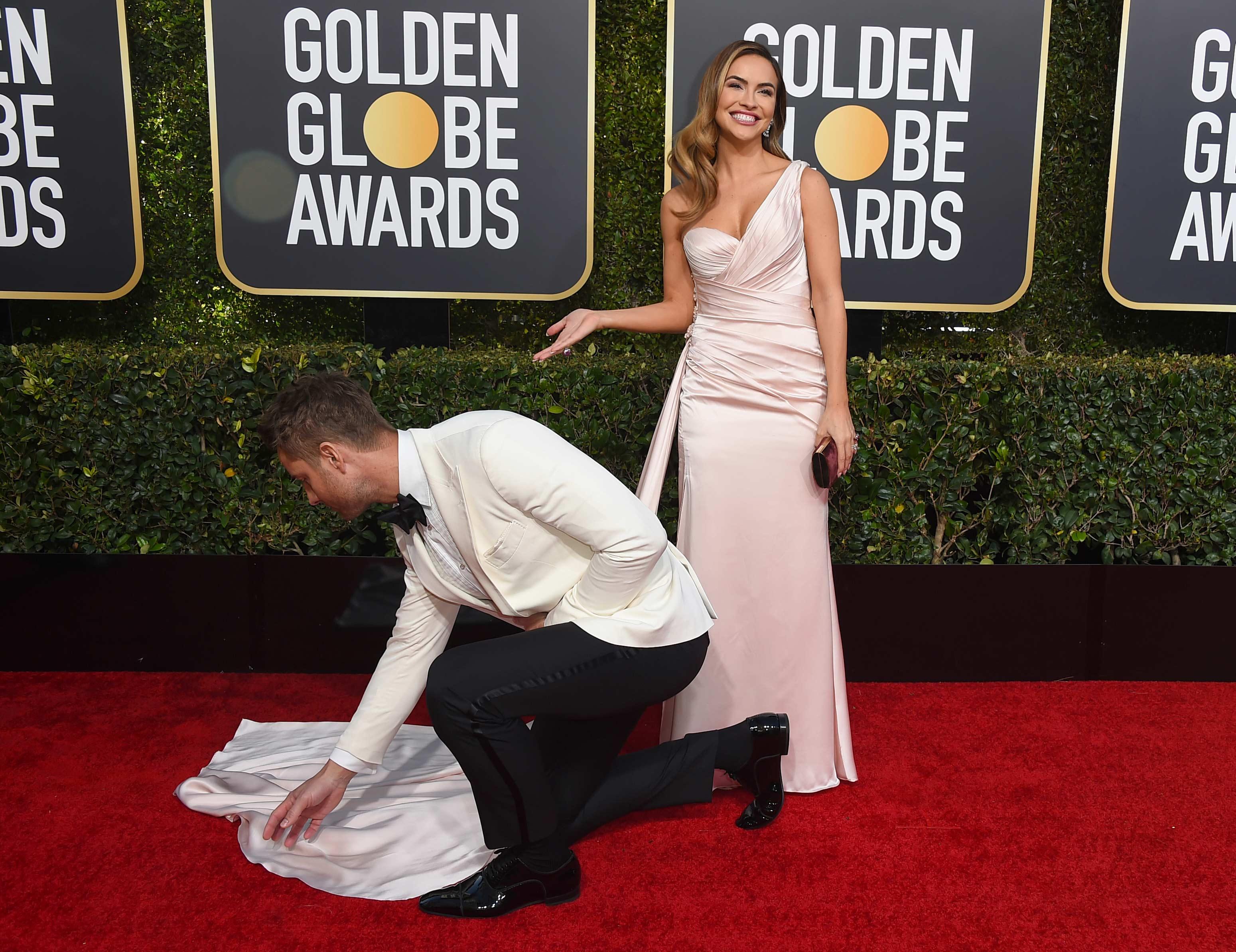 El actor Justin Hartley acomoda la cola del vestido de su pareja hace cinco años, la actriz Chrishell Stause. (Foto: AP)
