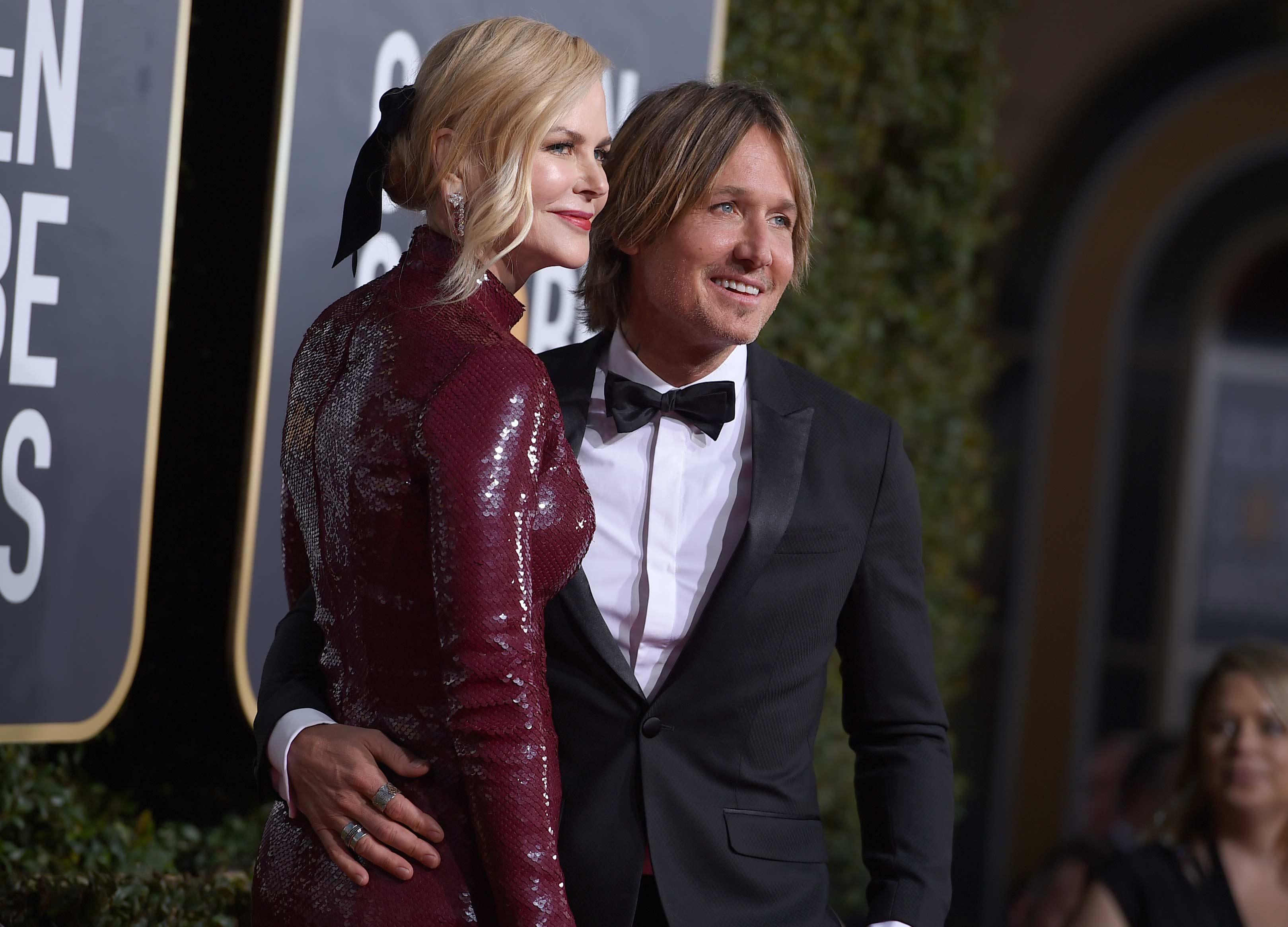 La actriz Nicole Kidman abraza a su esposo el músico Keith Urban al llegar a la alfombra roja de los Golden Globe. (Foto: AP)