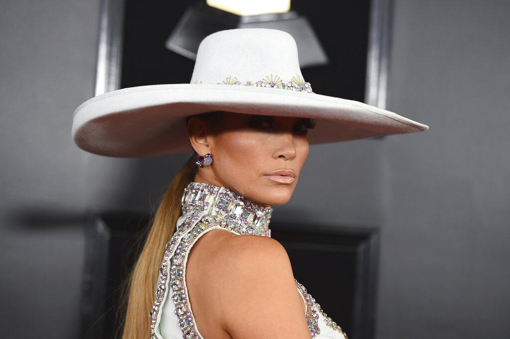 JLo acompañó su impactante vestido con un sombrero de ala ancha también bordado en cristales haciendo juego. (Foto: AP)