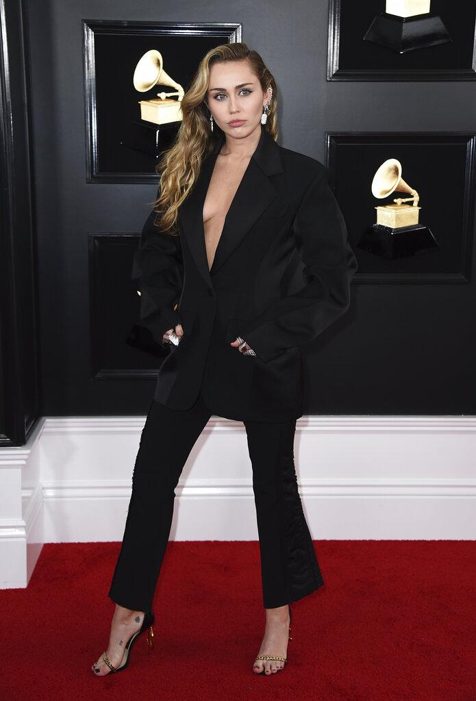Miley Cyrus también eligió pantalones, pero en color negro y con la chaqueta, sin nada debajo, haciendo juego. (Foto: AP)
