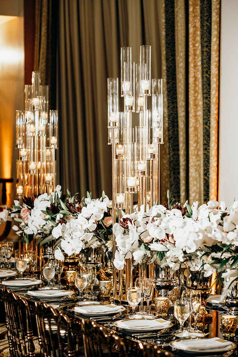 La elegante decoración de Akua, con majestuosos candelabros con velas, sillas doradas y flores blancas. Fotografía Esteban Daniel Photography